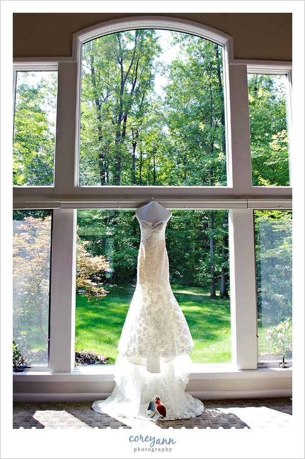 wedding dress hanging in window with shoes