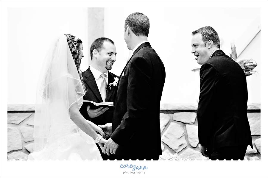 best man laughing as he hands rings to pastor during wedding ceremony