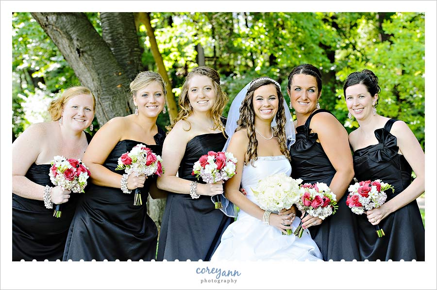 bridesmaids in black dresses with hot pink and white bouquets