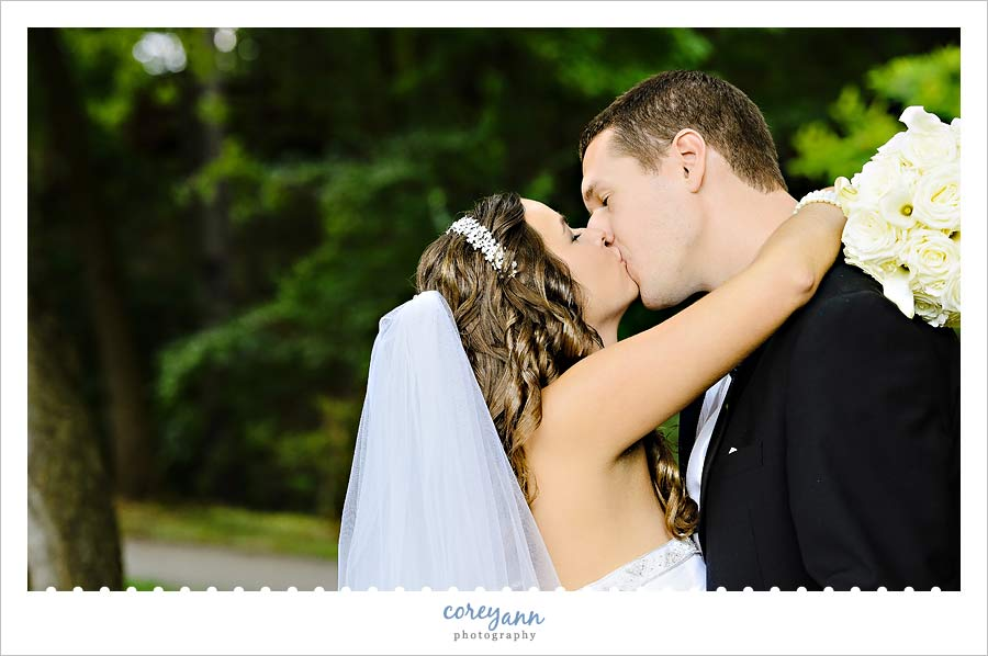 bride and groom kissing for portraits at canton garden center