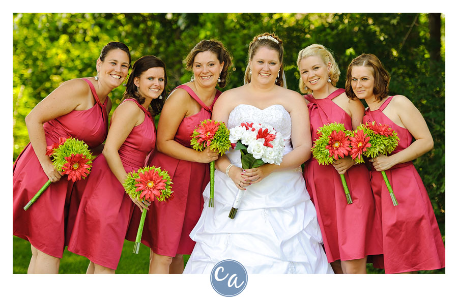 bride with bridesmaids in pink dresses outside