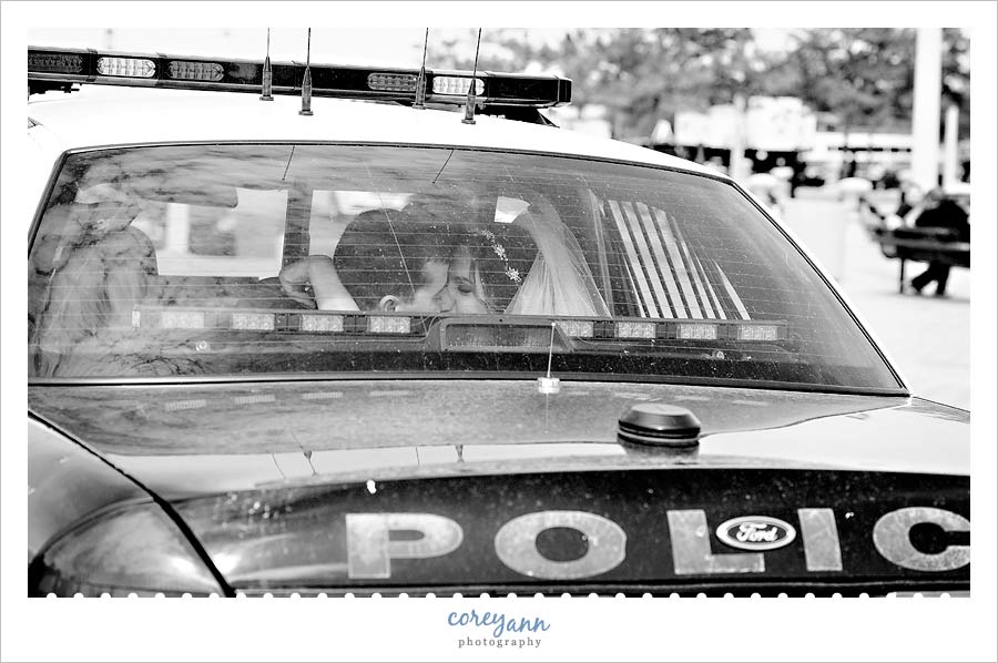 bride and groom in the back of a police cruiser