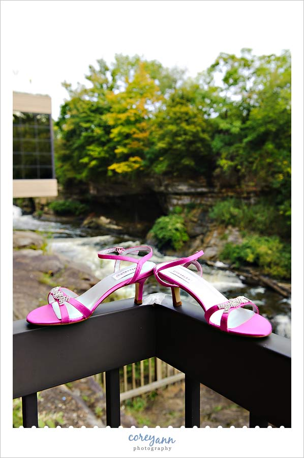 pink wedding shoes outside near waterfalls