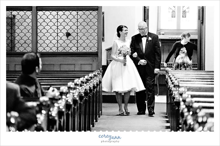 bride and father walking up the aisle to wedding ceremony at old stone church